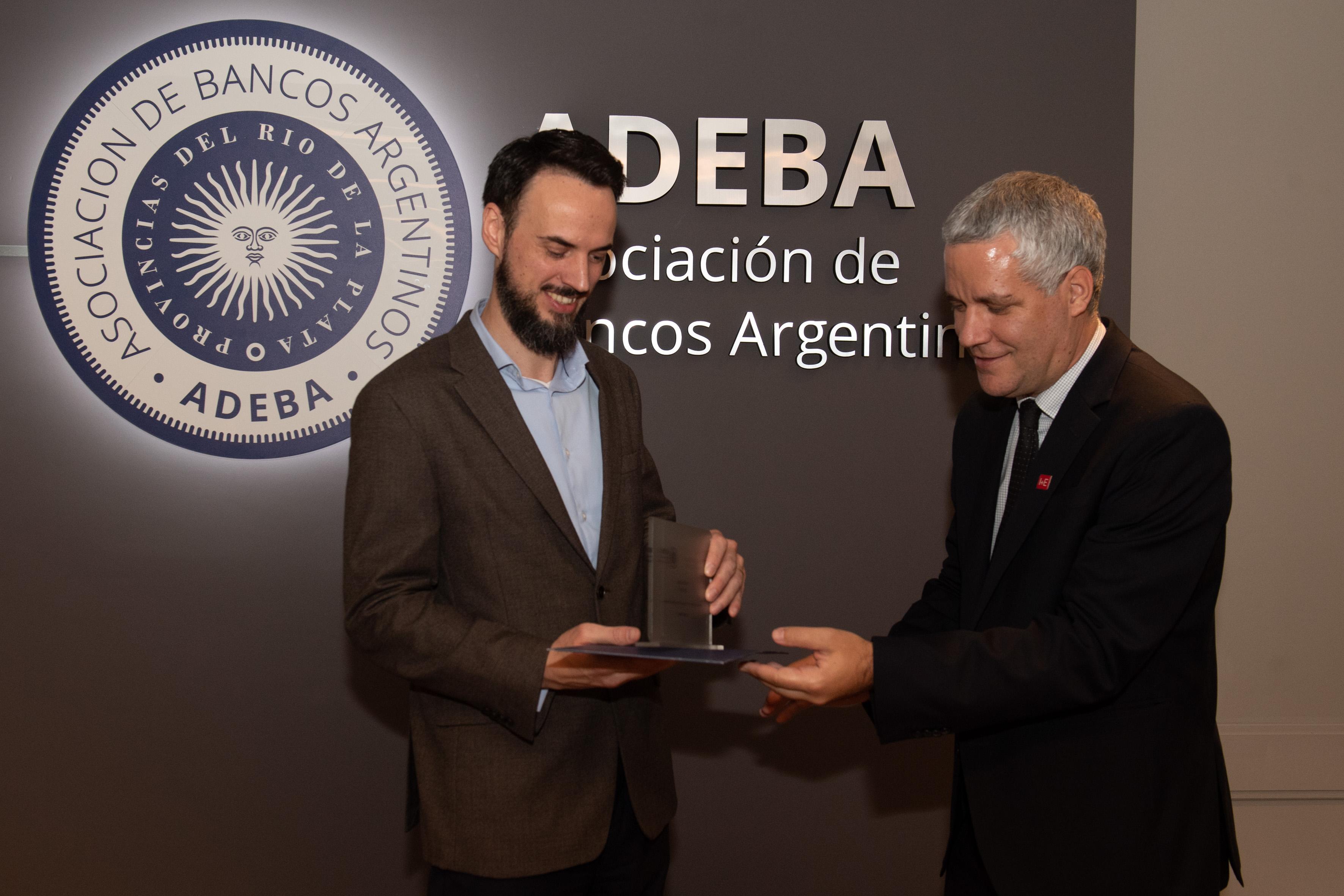 Emiliano Delfau, del segundo lugar del Premio ADEBA recibe uno de los premios por parte de Lucas Pussetto, director académico del I+E