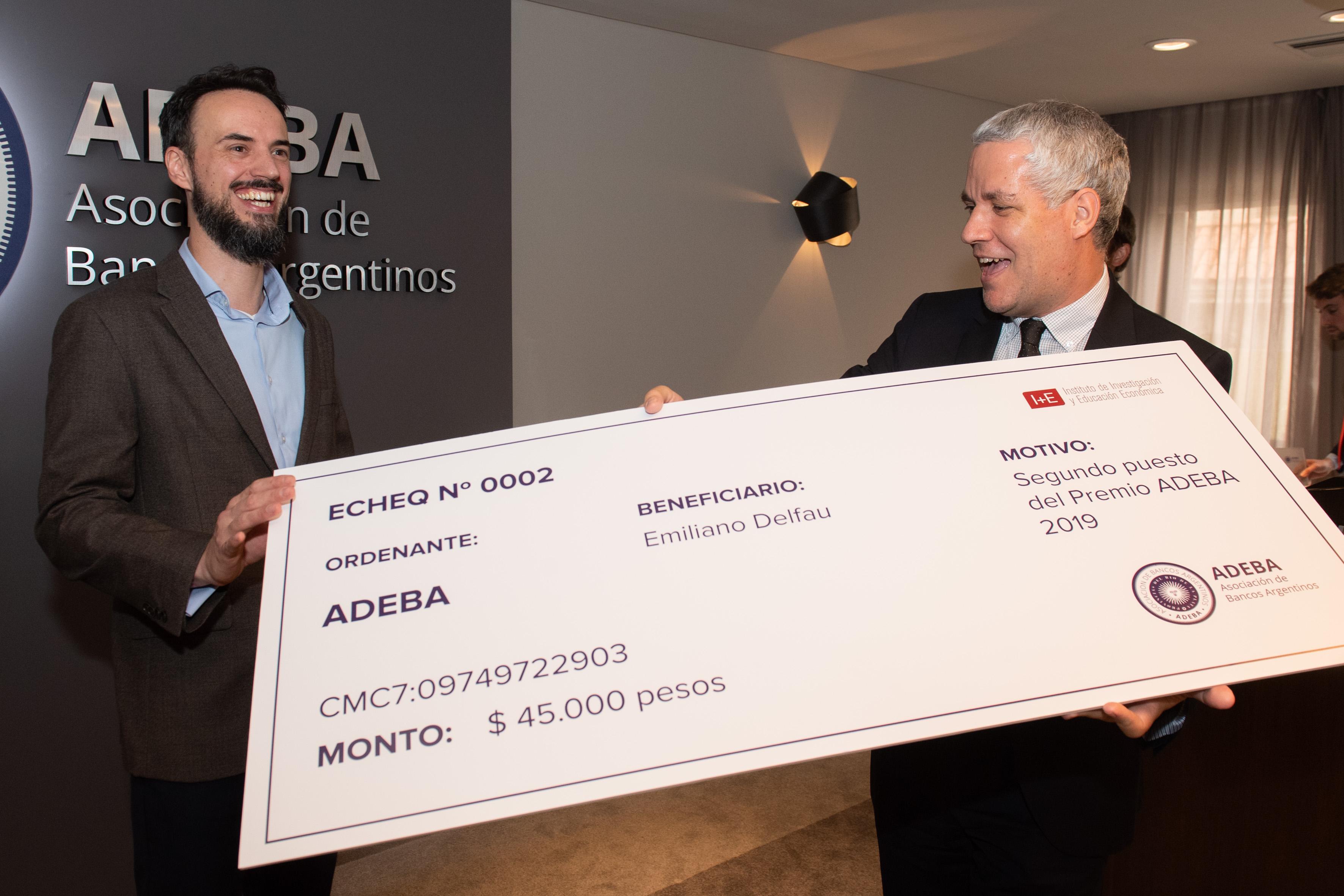 Emiliano Delfau, reconocido con el segundo lugar del Premio ADEBA junto a Lucas Pussetto, director académico del I+E, recibe el ECHEQ